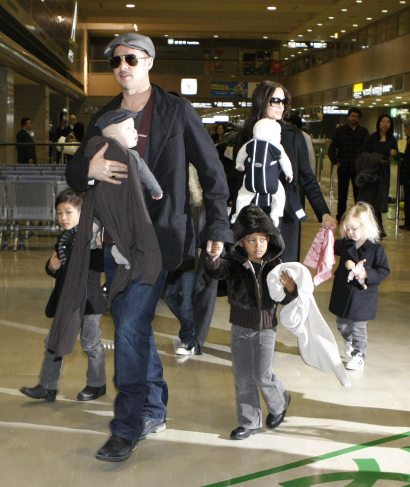 """U.S. actors Brad Pitt and Angelina Jolie arrive with their children at Narita airport, near Tokyo, January 27, 2009. Pitt is in Japan to promote the film """"The Curious Case of Benjamin Button"""". From L-R: Pax, Knox Leon (carried by Pitt), Maddox (obscured), Zahara, Vivienne Marcheline (carried by Jolie) and Shiloh.    REUTERS/Toru Hanai (JAPAN)"""