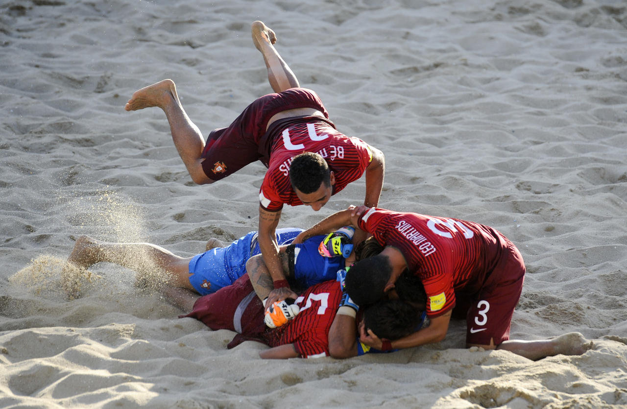 Portugal's Be Martins jumps over team players as they celebrate after winning the FIFA Beach Soccer World Cup final match in Espinho, Portugal, Sunday, July 19, 2015. Portugal beat Tahiti 5-3 to win the Beach Soccer World Cup.(AP Photo/Paulo Duarte)
