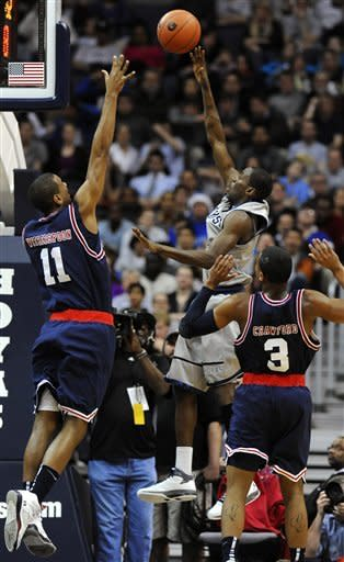 Georgetown's Jason Clark releases a baseline shot and scores as Memphis' Wesley Witherspoon (11) and Chris Crawford (3) defend during first half of an NCAA college basketball game Thursday, Dec. 22, 2011, in Washington. (AP Photo/Richard Lipski)