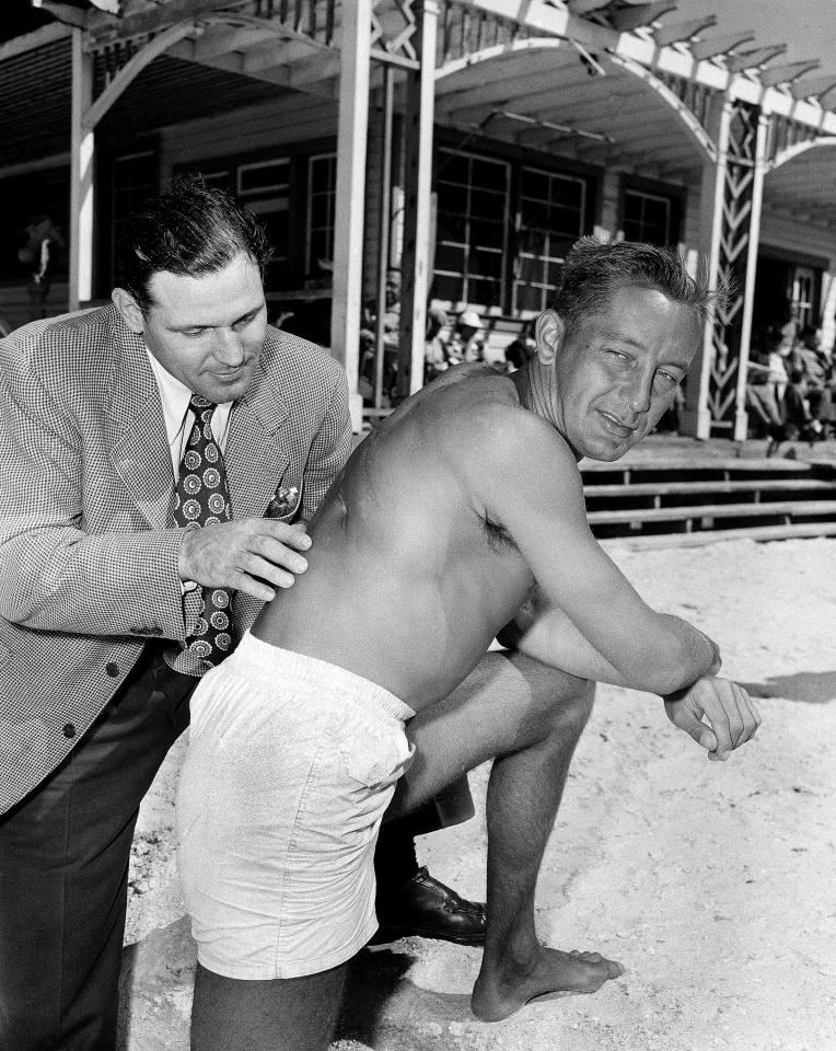 """FILE - In this Feb. 27, 1950 file photo, Philadelphia Phillies first baseman Eddie Waitkus, right, shows scars resulting from an operation following his shooting in Chicago in 1949, to his roommate, outfielder Bill Nicholson, on a beach in Clearwater, Fla. Waitkus was working his way back into condition at the team's spring training camp in Clearwater. Waitkus had been shot by 19-year-old Ruth Steinhagen at a hotel in one of the most sensational and bizarre criminal cases in Chicago history that made headlines around the country. Steinhagen died of natural causes at 83 in late December 2012. She was the inspiration for Bernard Malamud's novel """"The Natural"""" and the 1984 movie starring Robert Redford, a mysterious woman who lured a major league ballplayer she'd never met into a hotel room with a cryptic note and shot him. (AP Photo/File)"""