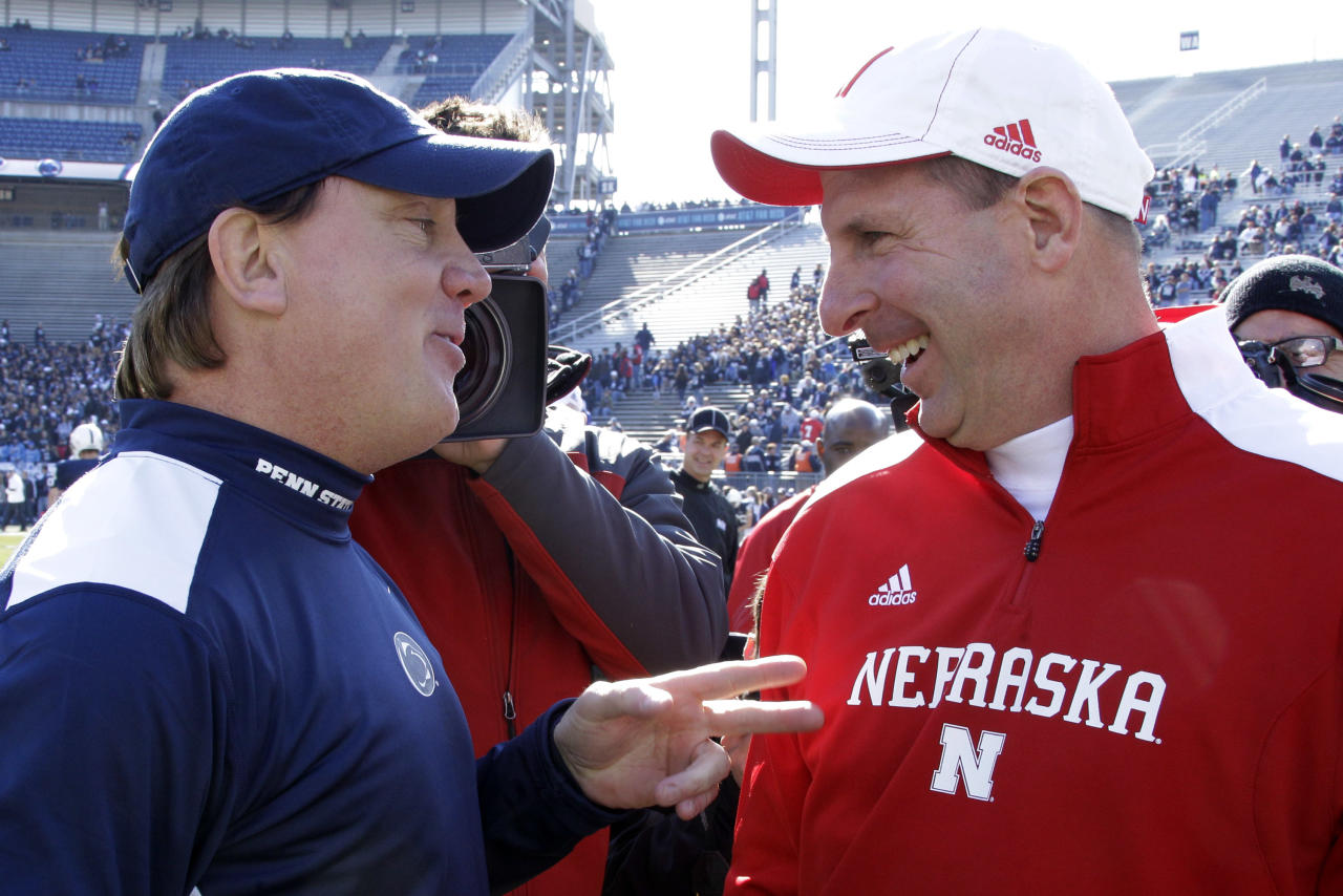 Penn State interim head coach Tom Bradley, left, talks with Nebraska head coach Bo Pelini during warm ups before an NCAA college football game at State College, Pa., Saturday, Nov. 12, 2011. (AP Photo/Gene J. Puskar)