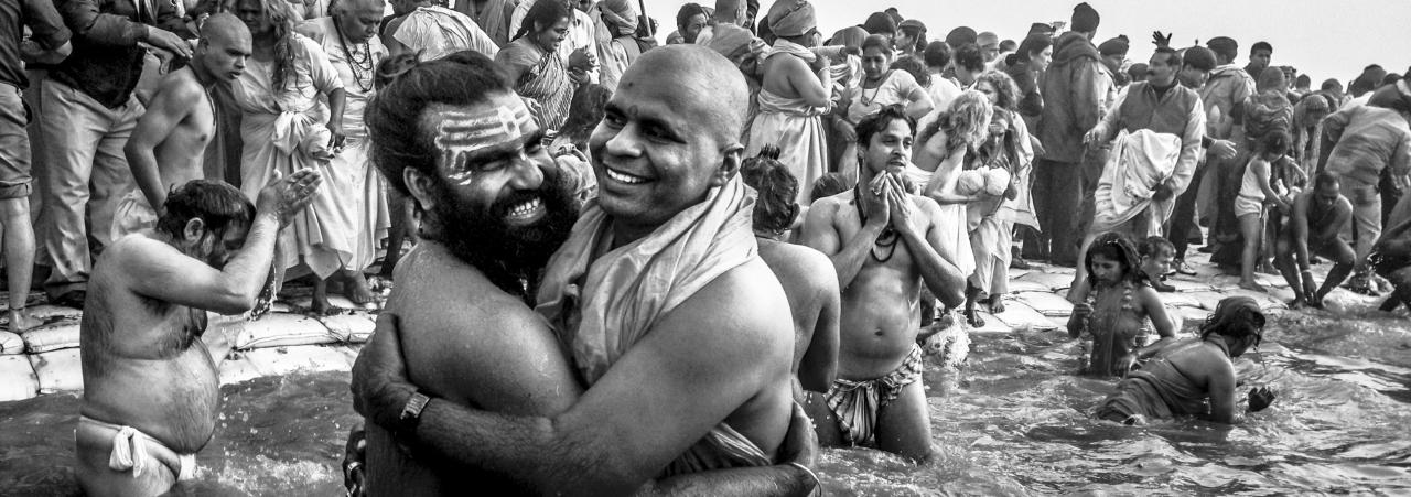 ALLAHABAD, INDIA - JANUARY 14: (EDITORS NOTE: Image was created using the iPhone panoramic application) Naga sadhus embrace as others bathe in the waters of Sangam during the auspicious bathing day of Makar Sankranti of the Maha Kumbh Mela on January 14, 2013 in Allahabad, India. The Maha Kumbh Mela, believed to be the largest religious gathering on earth is held every 12 years on the banks of Sangam, the confluence of the holy rivers Ganga, Yamuna and the mythical Saraswati. The Kumbh Mela alternates between the cities of Nasik, Allahabad, Ujjain and Haridwar every three years. The Maha Kumbh Mela celebrated at the holy site of Sangam in Allahabad, is the largest and holiest, celebrated over 55 days, it is expected to attract over 100 million people. (Photo by Daniel Berehulak/Getty Images)