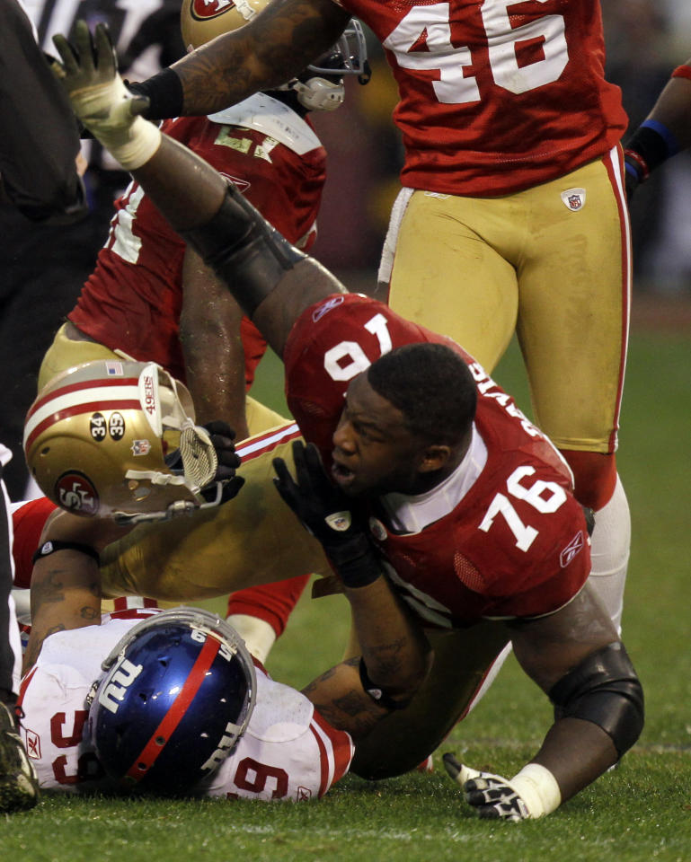 San Francisco 49ers' Anthony Davis (76) loses his helmet as he scuffles with New York Giants' Michael Boley (59) during the first half of the NFC Championship NFL football game Sunday, Jan. 22, 2012, in San Francisco. (AP Photo/Julie Jacobson)