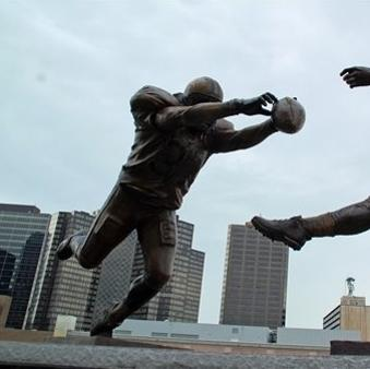 """This photo released July 27, 2012 by the New Orleans Saints shows the blocked punt that etched Steve Gleason into New Orleans Saints lore, and the symbolic significance that play took on in a city just starting to recover from disaster, is now immortalized in a nine-foot statue outside the Superdome. Gleason, who now has ALS, famously blocked the ball off of the foot of then-Atlanta punter Michael Koenen and into the end zone for a Saints touchdown on Sept. 25, 2006, the night the rebuilt Superdome and the city of New Orleans hosted an NFL game for the first time since Hurrciane Katrina. The statue, entitled """"Rebirth,"""" depicts Gleason fully outstretched in a dive, his hands smothering the ball as it leaves Koenen's foot.  Gleason says the statue is symbolizes the commitment of those who returned to rebuild after the storm. (AP Photo/New Orleans Saints, Alex Restrepo)"""