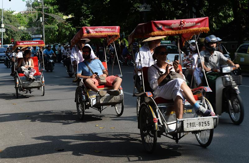 Tourists tour downtown Hanoi on July 16, 2014