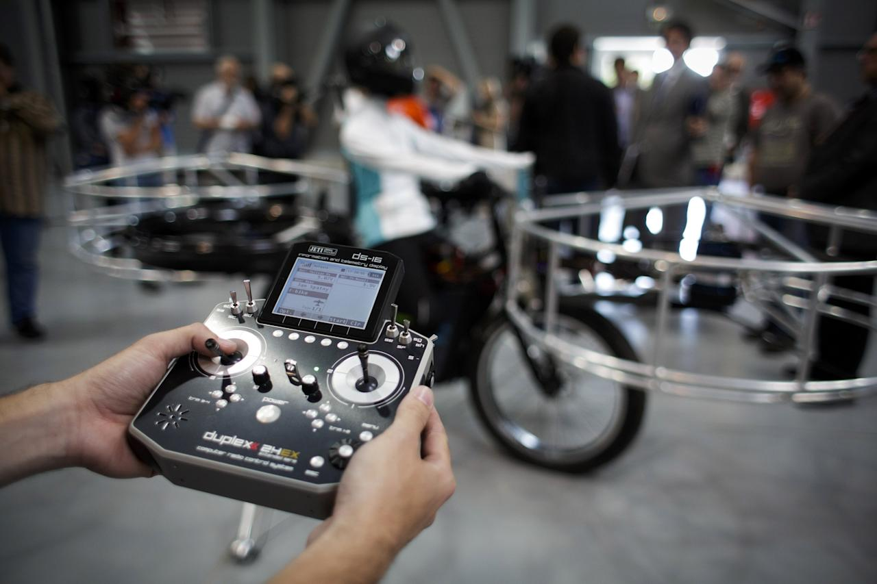 A technician holds the remote control for a 'Flying bike' bicycle ahead of its first public flight on June 12, 2013 in Prague, Czech Republic. The bike has been manufactured by 3 different companies from the Czech Republic (Duratec, Technodat, Evektor) and has been supported by French Company Dassault System. The F-Bike has four main motors (10kW) and two stabilization motors (3,5 kW). It has an estimated constant flight time of 3-5 minutes.  (Photo by Matej Divizna/Getty Images)