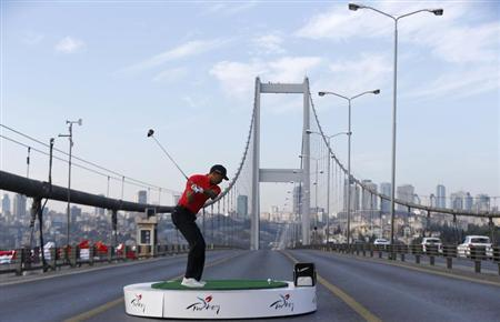 U.S. golfer Tiger Woods hits a shot during an event to promote the upcoming Turkish Airlines Open golf tournament, on the Bosphorus Bridge that links the city's European and Asian sides, in Istanbul
