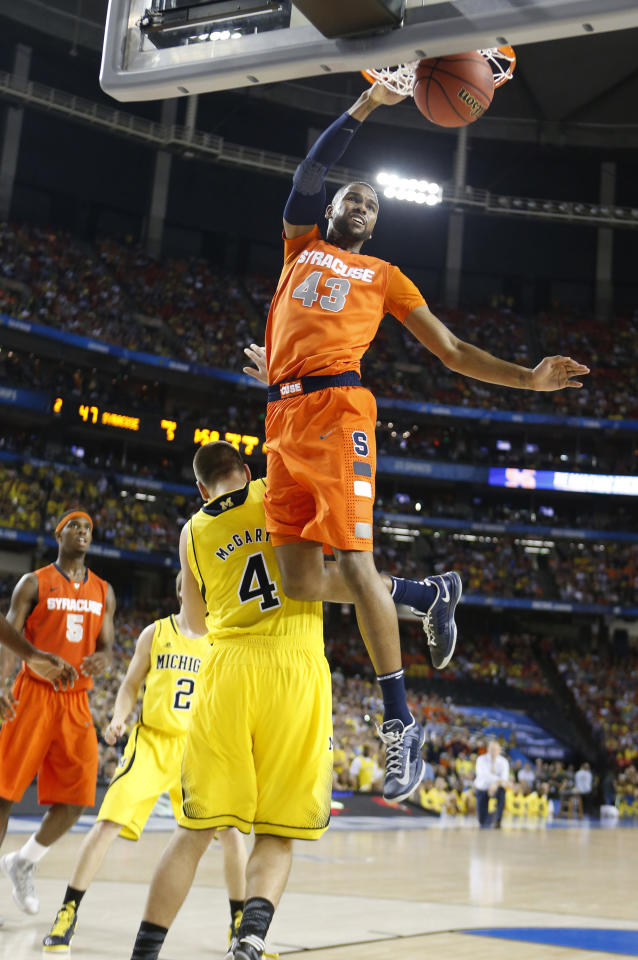 James Southerland (43) of the Syracuse Orange dunks over Mitch McGary (4) of the Michigan Wolverines late in the game in an NCAA Final Four semifinal at the Georgia Dome in Atlanta, Georgia, Saturday, April 6, 2013.