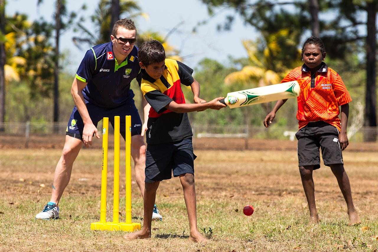 DARWIN, AUSTRALIA - AUGUST 10:  Peter Siddle of the Australian cricket team plays cricket with children during a visit to Pirlangimpi of the Tiwi Islands on August 10, 2012 on the Tiwi Islands, Australia.  (Photo by Mark Nolan/Getty Images)