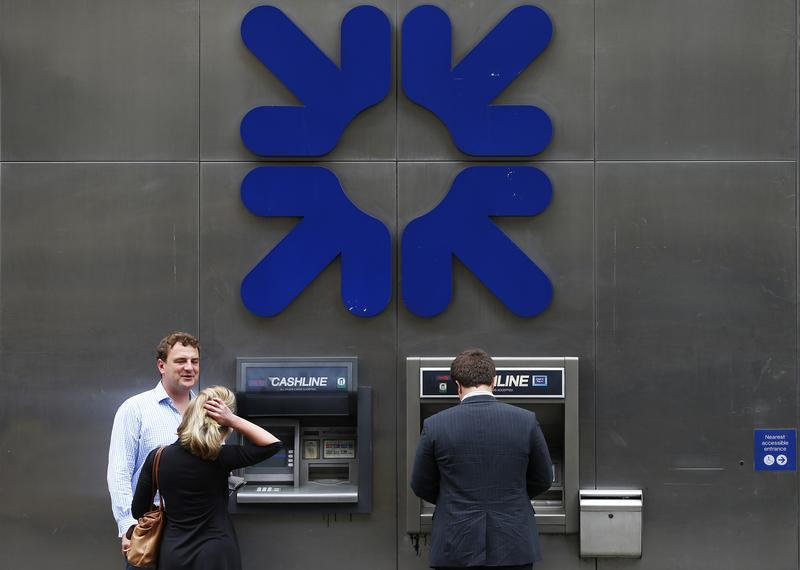A man uses a cashpoint machine outside a branch of the Royal Bank of Scotland in the City of London