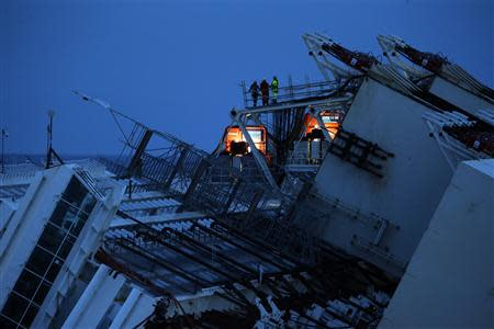 Salvage crew workers are seen on a side of the capsized cruise liner Costa Concordia outside Giglio harbour September 16, 2013. REUTERS/Tony Gentile