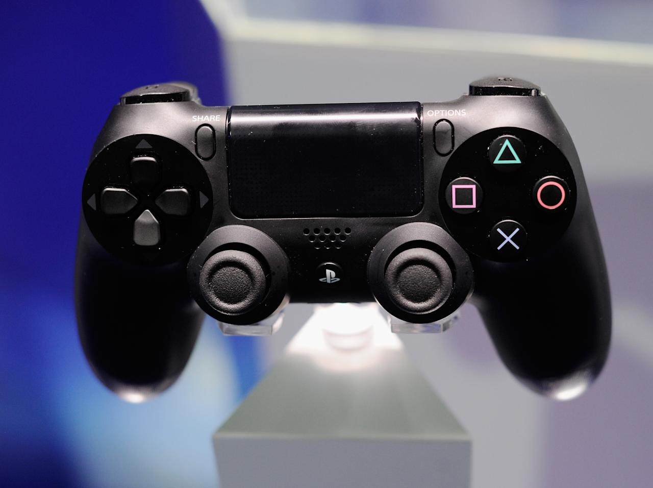LOS ANGELES, CA - JUNE 11: A Playstation 4 and its controller is on display at the Sony Playstation E3 2013 booth at the Los Angeles Convention Center on June 11, 2013 in Los Angeles, California. Thousands are expected to attend the annual three-day convention to see the latest games and announcements from the gaming industry. (Photo by Kevork Djansezian/Getty Images)