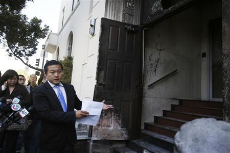 Wang Chuan, a spokesman for the Chinese consulate in San Francisco, points to a damaged door in San Francisco