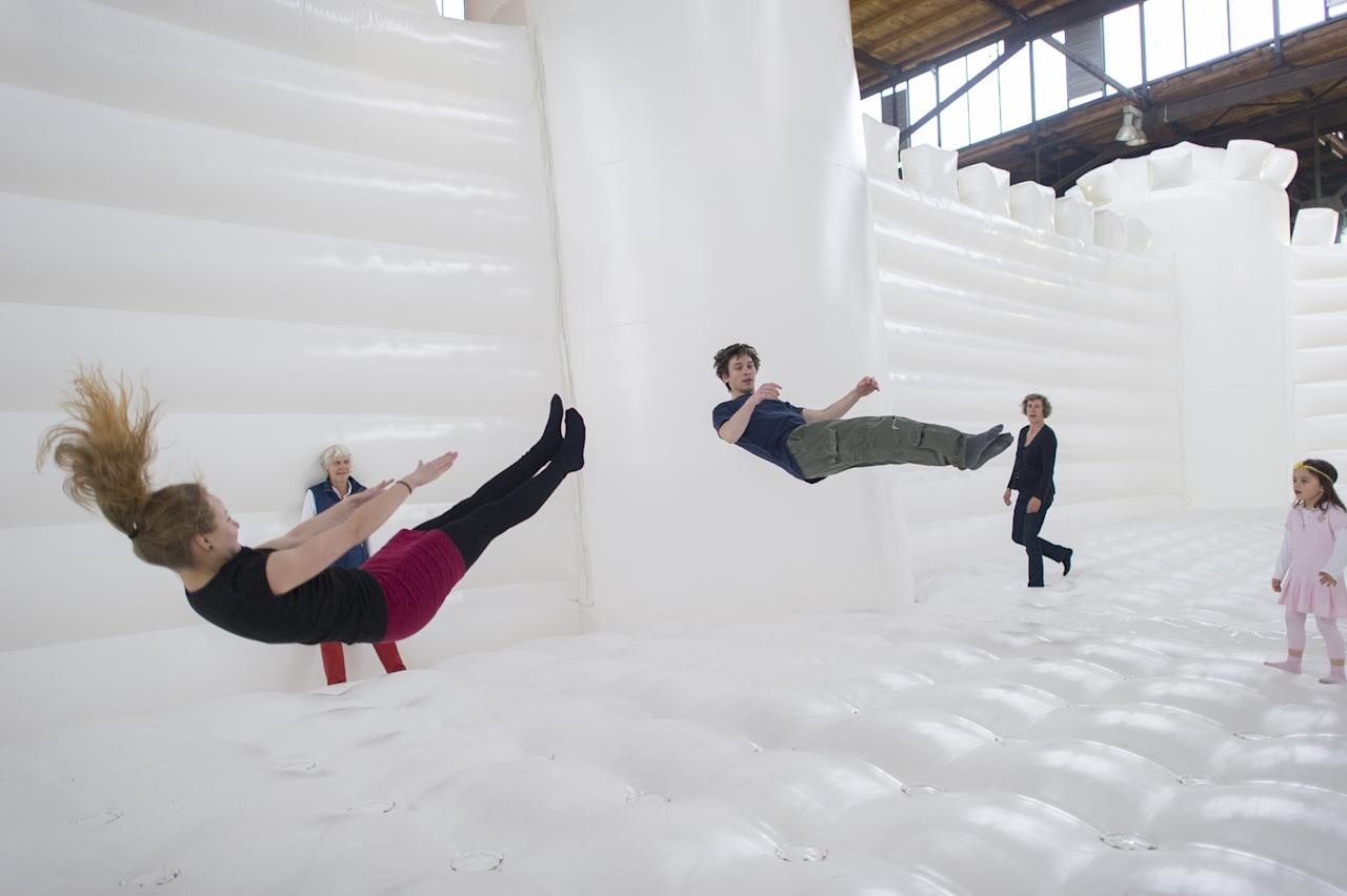 """BERLIN, GERMANY - JUNE 27: Visitors jump in the """"White Bouncy Castle"""" of installation artist William Forsythe on June 27, 2013 in Berlin, Germany. The work is a giant, inflatable white castle that Forsythe says encourages people to dance the moment they step into it. """"White Bouncy Castle"""" will be open to visitors at Lokhalle Schoeneberg until July 14 and is part of the """"Foreign Affairs"""" series of Berliner Festspiele. (Photo by Timur Emek/Getty Images)"""