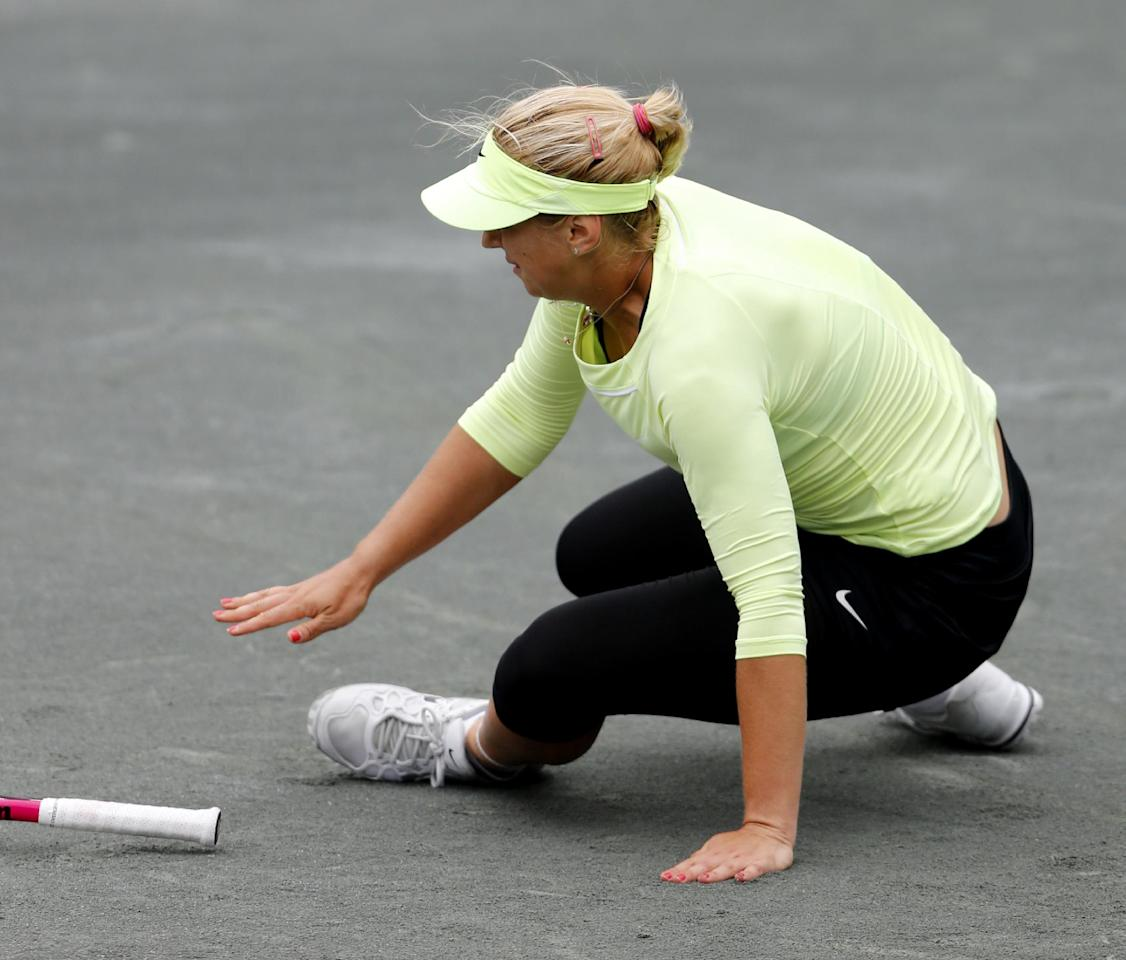 Sabine Lisicki, of Germany, falls to the ground after twisting her left ankle during her quarterfinals match against Serena Williams at the Family Circle Cup tennis tournament in Charleston, S.C., Friday, April 6, 2012. Lisicki later withdrew from the match. (AP Photo/Mic Smith)