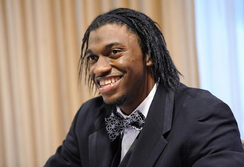 Washington Redskins quarterback Robert Griffin III, the team's Ed Block Courage Award winner, smiles during an autograph session at the Ed Block Courage Awards banquet in Baltimore Monday, March 17, 2014. The award, named for the late former trainer of the Baltimore Colts, recognizes a player from each team in the National Football League who has displayed courage in the face of adversity over the past year