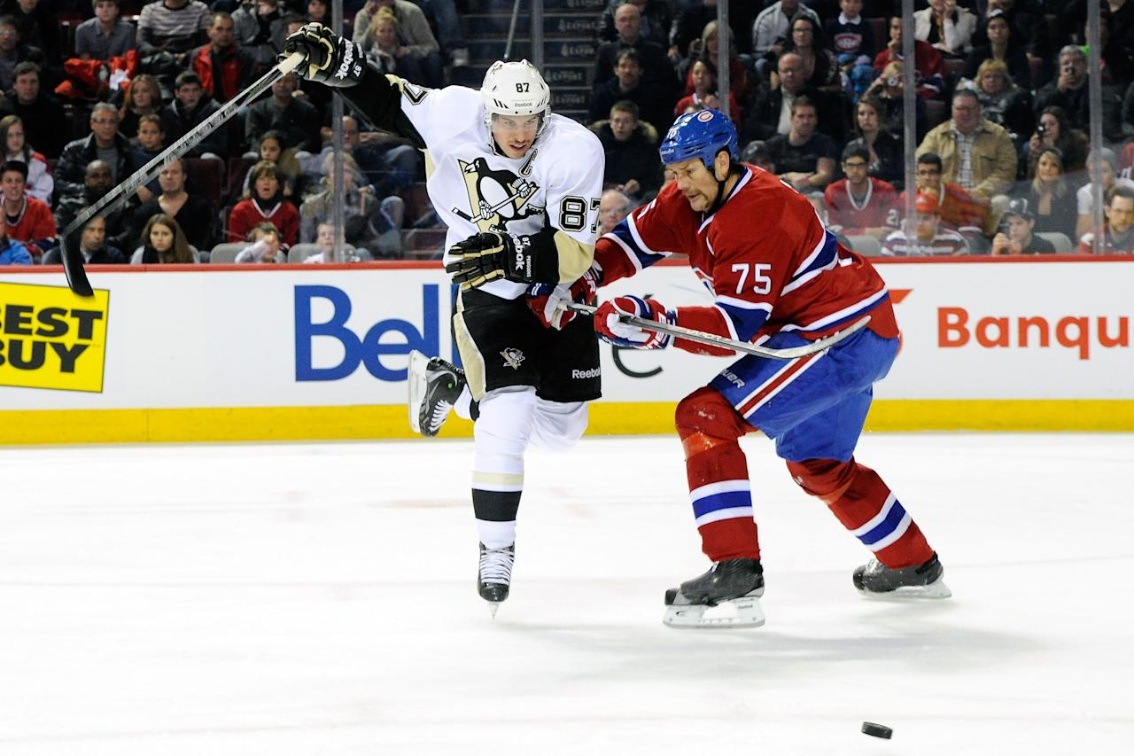 MONTREAL, CANADA - NOVEMBER 26:  Sidney Crosby #87 of the Pittsburgh Penguins chases the puck while being defended by Hal Gill #75 of the Montreal Canadiens during the NHL game at the Bell Centre on November 26, 2011 in Montreal, Quebec, Canada.  (Photo by Richard Wolowicz/Getty Images)