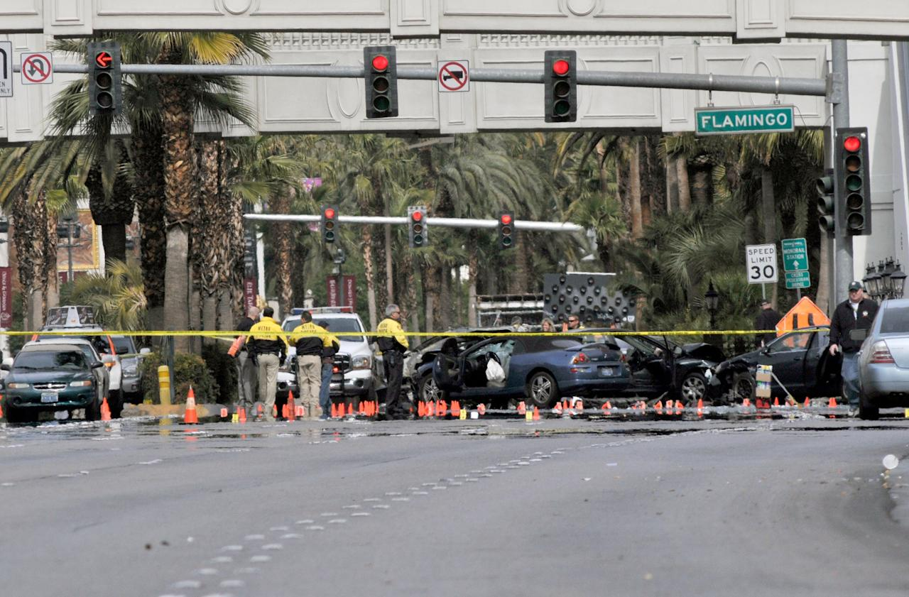 LAS VEGAS, NV - FEBRUARY 21:  Las Vegas Metro officers investigate the site of what is being described as a gun battle between shooters in vehicles along the Las Vegas Strip on February 21, 2013 in Las Vegas, Nevada. According to reports gunshots were fired between black SUV at a Maserati, causing the Maserati to crash into a taxi, that burst into flames. Five vehicles were involved in the subsequent crash with the Maserati driver and two people in the taxi being killed.  (Photo by David Becker/Getty Images)
