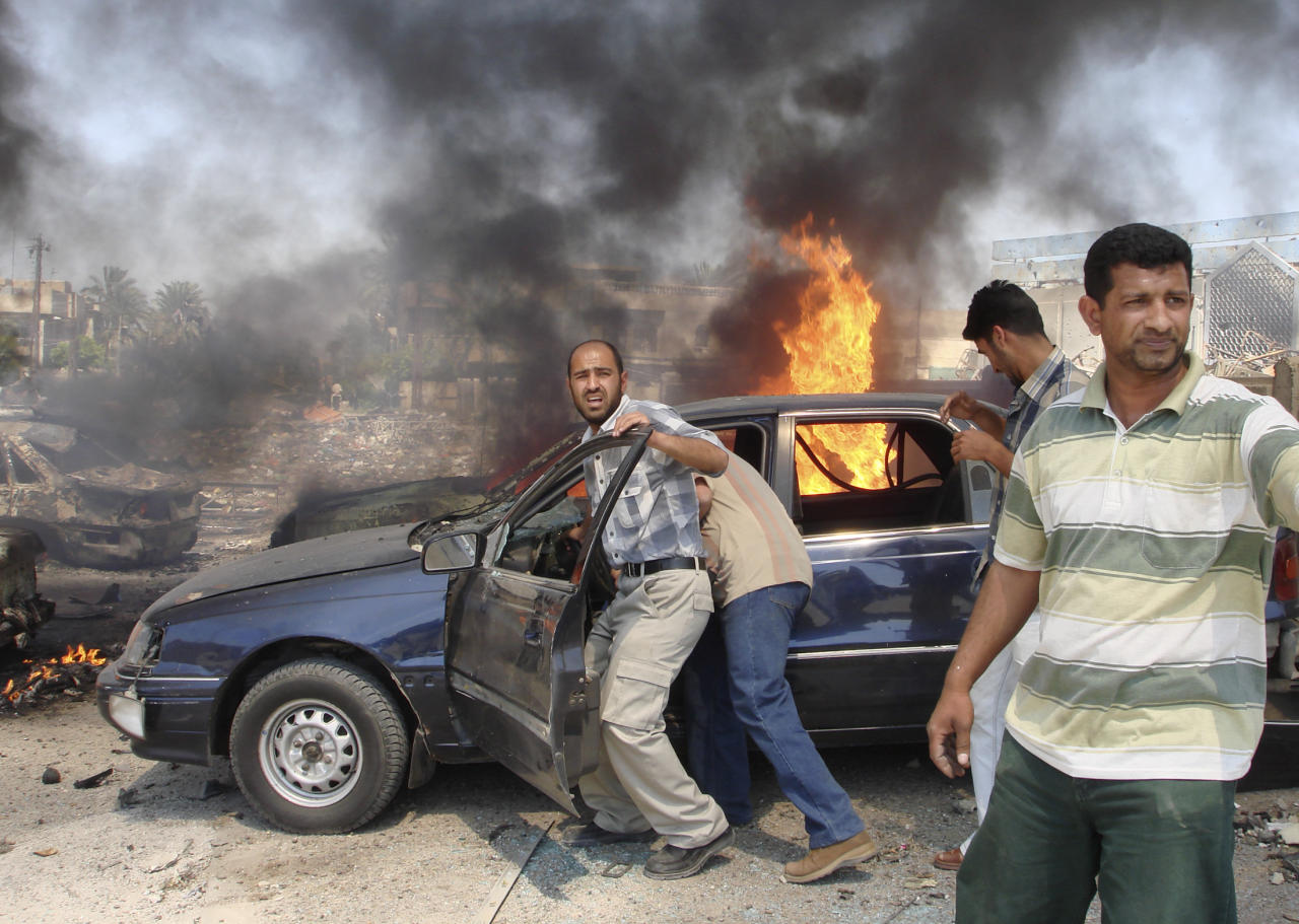 Men try to push a vehicle away from the scene of a suicide bomb attack in Baghdad, April 5, 2007. A Baghdad satellite television station run by Iraq's biggest Sunni political party briefly went off the air on Thursday after a suicide truck bomb exploded nearby, killing one person and wounding three.    REUTERS/Stringer (IRAQ)