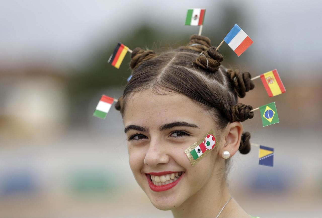 A fan with the flags of Italy, Germany, Mexico, the Netherlands, Spain, Brazil and Bosnia in her hair smiles prior to the group A World Cup soccer match between Brazil and Mexico at the Arena Castelao in Fortaleza, Brazil, Tuesday, June 17, 2014. (AP Photo/Themba Hadebe)