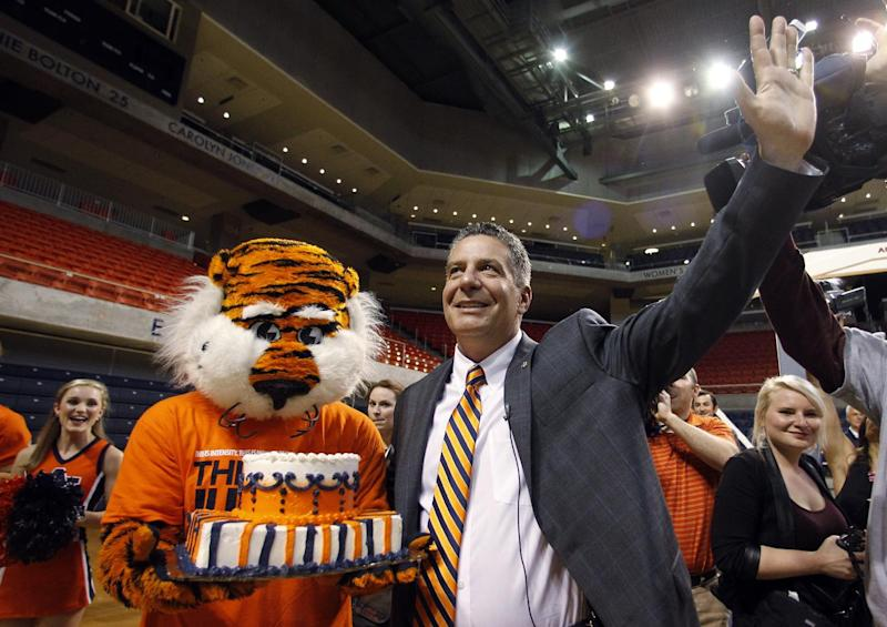 Auburn's new men's basketball coach, Bruce Pearl, waves to fans after he received a birthday cake from Auburn mascot Aubie on Tuesday, March 18, 2014, in Auburn, Ala