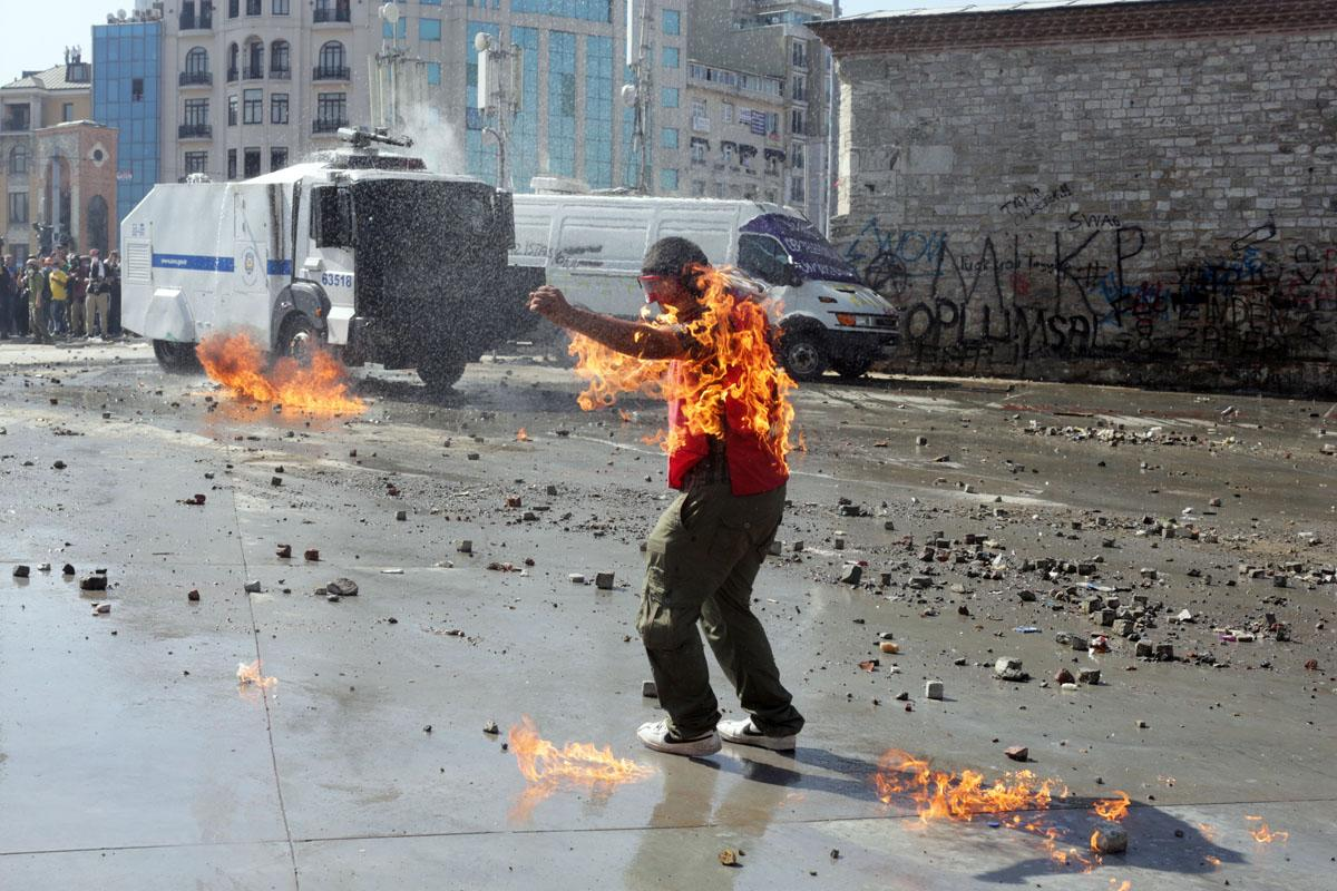 A demonstrator's clothes are set on fire during clashes with riot police in Taksim square on June 11, 2013. Riot police stormed Istanbul's protest square on june 11, firing tear gas and rubber bullets at firework-hurling demonstrators in a fresh escalation of unrest after Turkish Prime Minister Recep Tayyip Erdogan said he would meet with protest leaders.    AFP PHOTO / OREN ZIV