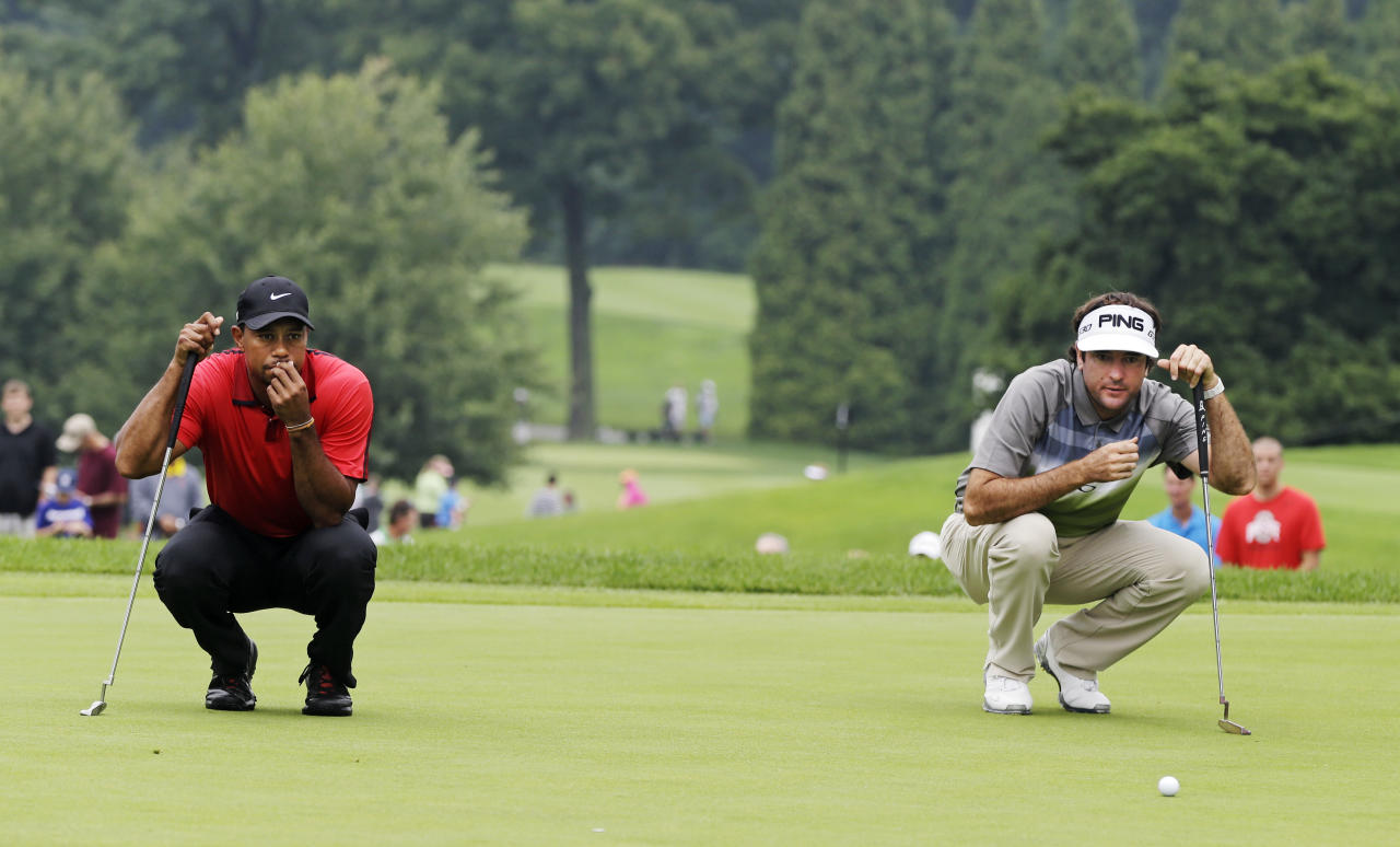Tiger Woods, left, and Bubba Watson looks over their putts on the second hole during the final round of the Bridgestone Invitational golf tournament Sunday, Aug. 3, 2014, at Firestone Country Club in Akron, Ohio. (AP Photo/Mark Duncan)