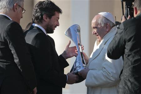 A member of Argentine soccer team San Lorenzo presents Pope Francis with the replica of the trophy that they won in the Argentine soccer championship, during the Wednesday general audience in Saint Peter's square at the Vatican