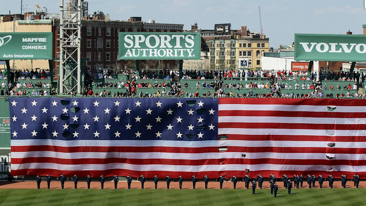 BOSTON, MA - APRIL 20:  A giant flag covers the Green Monster as the national anthem is played before the game between the New York Yankees and the Boston Red Sox on April 20, 2012 at Fenway Park in Boston, Massachusetts. Today marks the 100 year anniversary of the ball park's opening.  (Photo by Elsa/Getty Images)