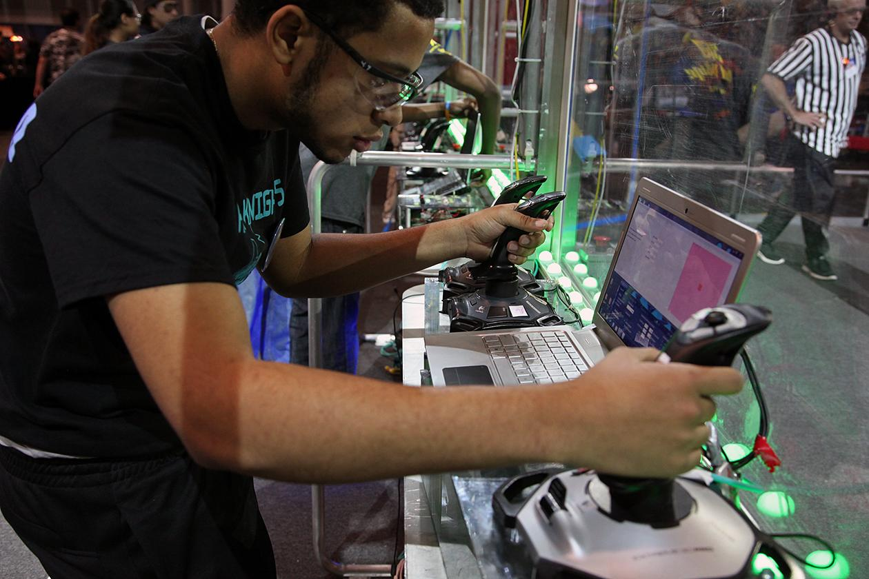 A robot driver calibrates his controls before the start of a match.