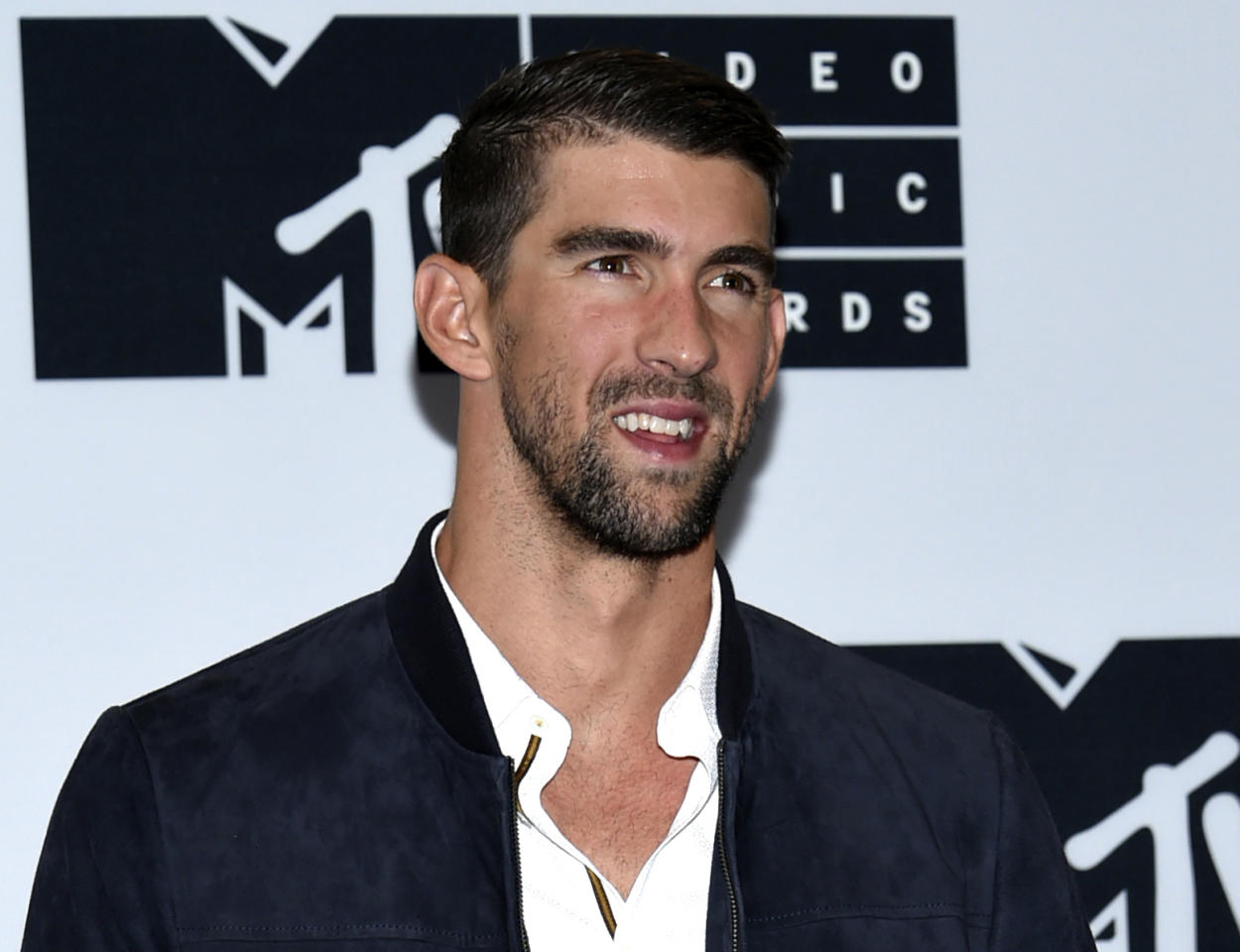 """FILE - In this Aug. 28, 2016 file photo, Michael Phelps poses in the press room at the MTV Video Music Awards in New York. Phelps will be named Sports Illustrated's """"Person of the Year"""" at a ceremony on Monday, Dec. 12. (Photo by Evan Agostini/Invision/AP, File)"""
