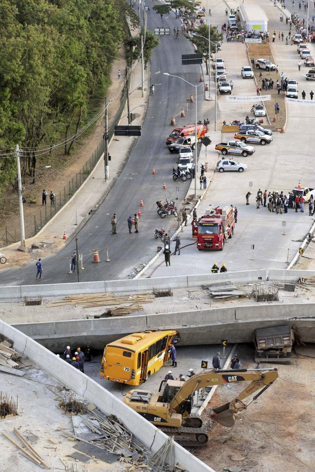 Rescue workers try to reach vehicles trapped underneath a bridge that collapsed while under construction in Belo Horizonte July 3, 2014. An unfinished overpass collapsed in the Brazilian World Cup host city of Belo Horizonte on Thursday, killing at least two people, emergency officials said. REUTERS/Carlos Greco-DYN (BRAZIL - Tags: DISASTER SPORT SOCCER WORLD CUP BUSINESS CONSTRUCTION) ARGENTINA OUT. NO COMMERCIAL OR EDITORIAL SALES IN ARGENTINA