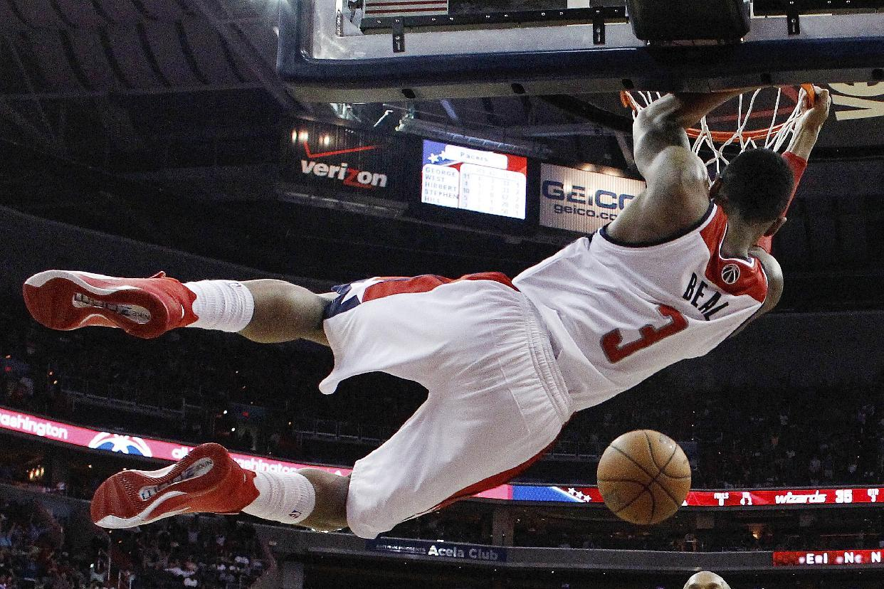 Washington Wizards guard Bradley Beal hangs from the basket after dunking the ball during the second half of Game 3 of an Eastern Conference semifinal NBA basketball playoff game against the Indiana Pacers in Washington, Friday, May 9, 2014. The Pacers won 85-63. (AP Photo/Alex Brandon)