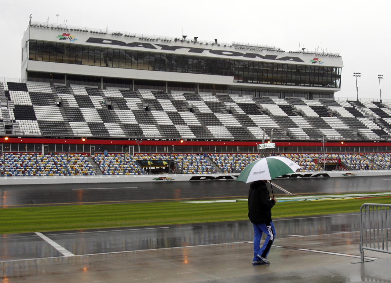 A crew member walks down pit road as officials hope to start the rain-postponed NASCAR Daytona 500 Sprint Cup series auto race in Daytona Beach, Fla., Monday, Feb. 27, 2012. NASCAR president Mike Helton says the Daytona 500 will start Monday night at 7 p.m. Heavy rain soaked Daytona International Speedway on Sunday, forcing NASCAR to postpone the event for the first time in its 54-year history.(AP Photo/Terry Renna)