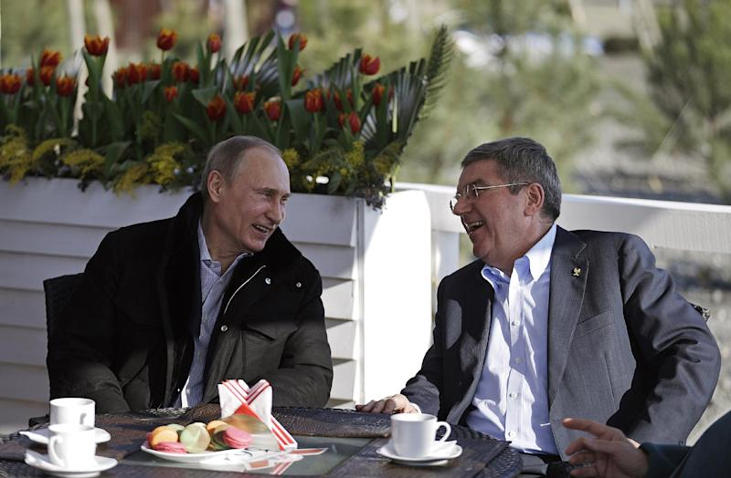 Russian President Vladimir Putin, left, and International Olympic Committee President Thomas Bach sit at a cafe along the promenade on the Black Sea near the Olympic Park at the 2014 Winter Olympics, Saturday, Feb. 15, 2014, in Sochi, Russia