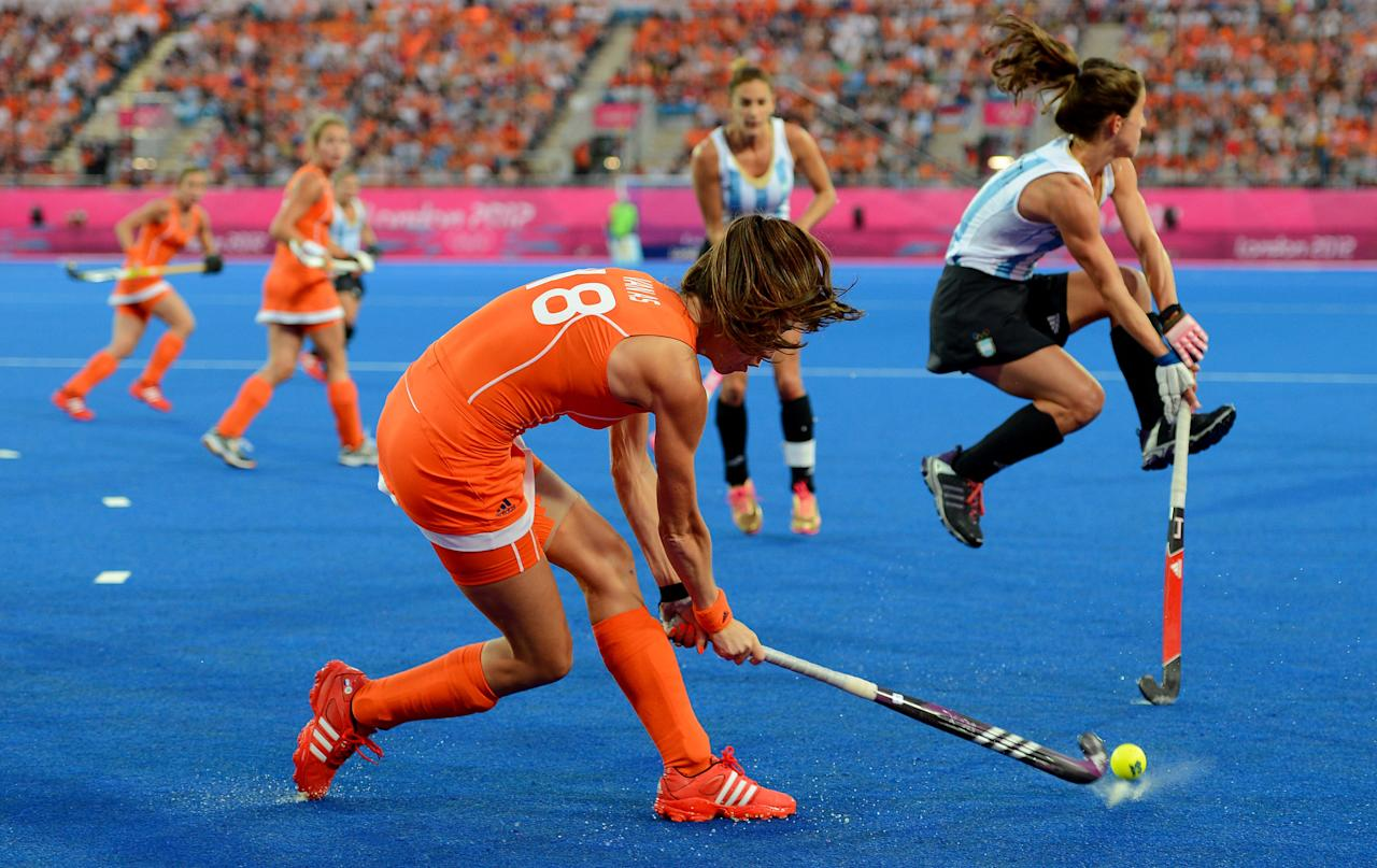 LONDON, ENGLAND - AUGUST 10:  Naomi Van As #18 of Netherlands passes the ball against Carla Rebecchi #11 of Argentina who jumps out of the way during the first half of the Women's Hockey gold medal match on Day 14 of the London 2012 Olympic Games at Hockey Centre on August 10, 2012 in London, England.  (Photo by Mike Hewitt/Getty Images)
