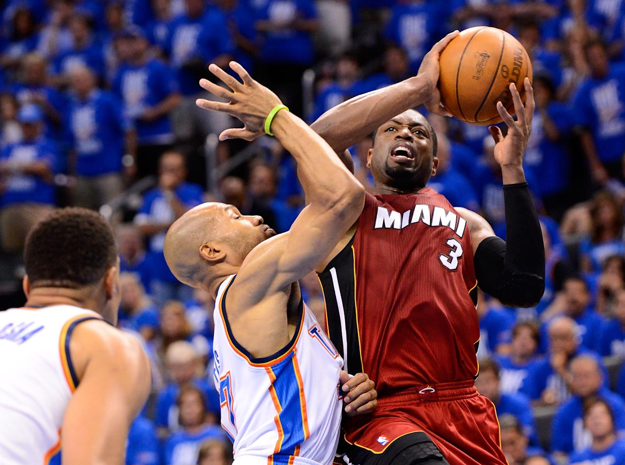 OKLAHOMA CITY, OK - JUNE 12:  Dwyane Wade #3 of the Miami Heat goes up for a shot over Derek Fisher #37 of the Oklahoma City Thunder in the second half in Game One of the 2012 NBA Finals at Chesapeake Energy Arena on June 12, 2012 in Oklahoma City, Oklahoma. NOTE TO USER: User expressly acknowledges and agrees that, by downloading and or using this photograph, User is consenting to the terms and conditions of the Getty Images License Agreement.  (Photo by Ronald Martinez/Getty Images)