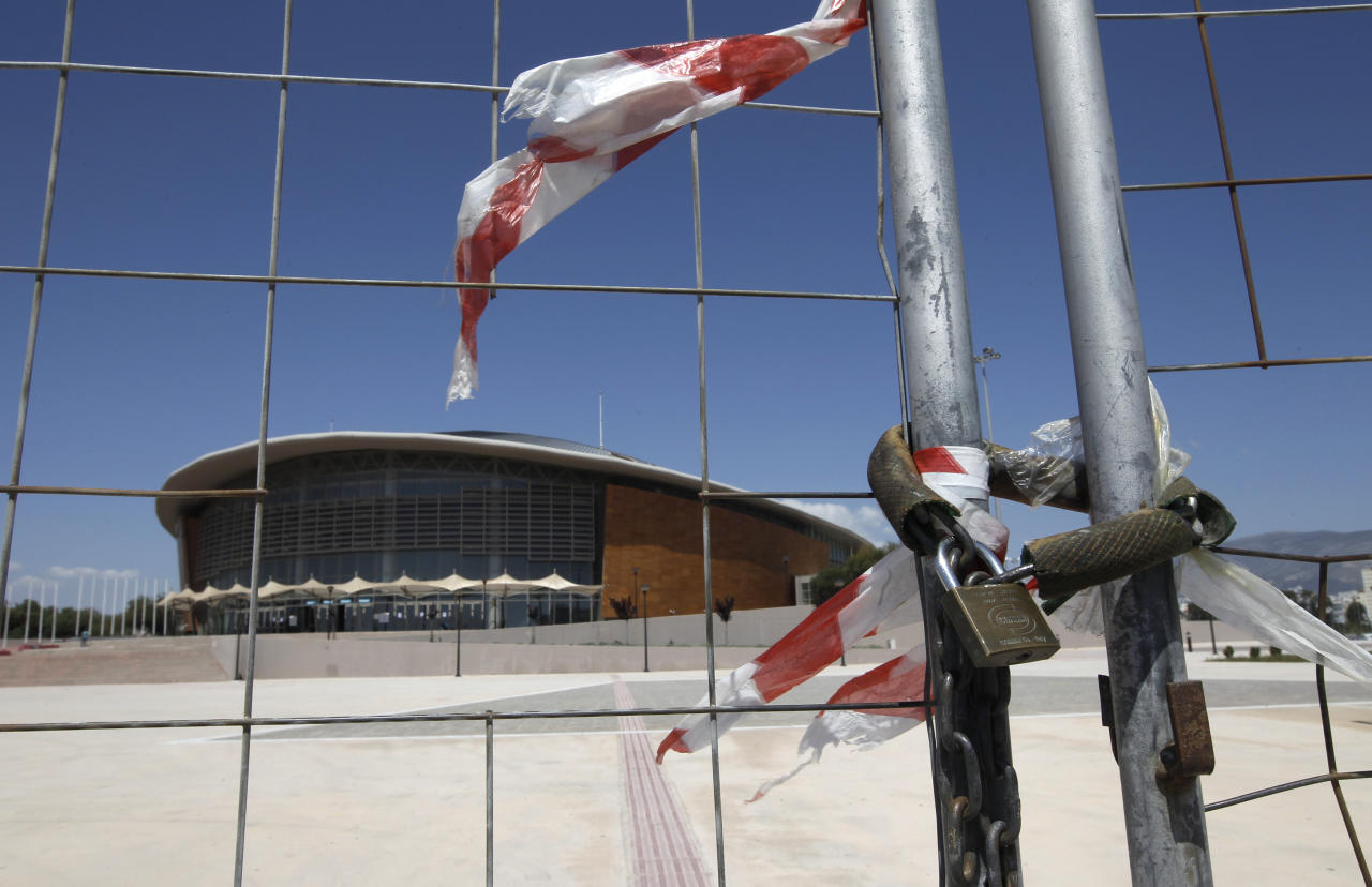 The Olympic Taekwondo stadium is seen behind a fence at Faliro complex in Athens, May 17 2011. Greece has pledged to its EU partners in March to target 50 billion euros from privatisations and real estate assets, including former Athens 2004 Olympics venues, by 2015 to help reduce its debt.   REUTERS/John Kolesidis