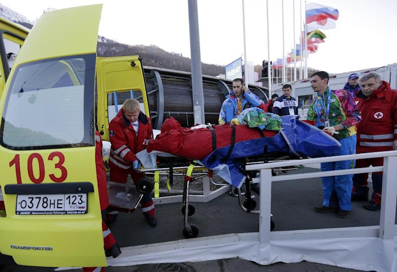 A track worker is loaded into an ambulance after he was injured when a forerunner bobsled hit him just before the start of the men's two-man bobsled training at the 2014 Winter Olympics, Thursday, Feb. 13, 2014, in Krasnaya Polyana, Russia