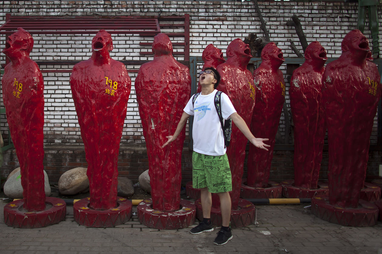 a man poses for photos in front of art pieces.