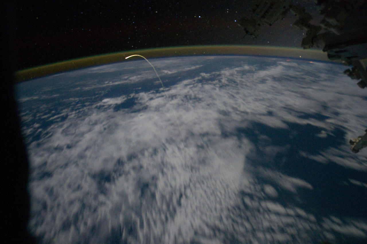 This unprecedented view of the space shuttle Atlantis, appearing like a bean sprout against clouds and city lights shows the shuttle on its way home as photographed by the Expedition 28 crew of the International Space Station through a window of the station in this July 21, 2011 NASA handout photo. Airglow over Earth can be seen in the background. The Atlantis and its four-member crew returned to the Kennedy Space Center in Florida on Thursday after a mission to resupply the International Space Station, ending a 12-year program to build and service the orbital research outpost.  REUTERS/NASA/Handout (SCI TECH IMAGES OF THE DAY) FOR EDITORIAL USE ONLY. NOT FOR SALE FOR MARKETING OR ADVERTISING CAMPAIGNS. THIS IMAGE HAS BEEN SUPPLIED BY A THIRD PARTY. IT IS DISTRIBUTED, EXACTLY AS RECEIVED BY REUTERS, AS A SERVICE TO CLIENTS