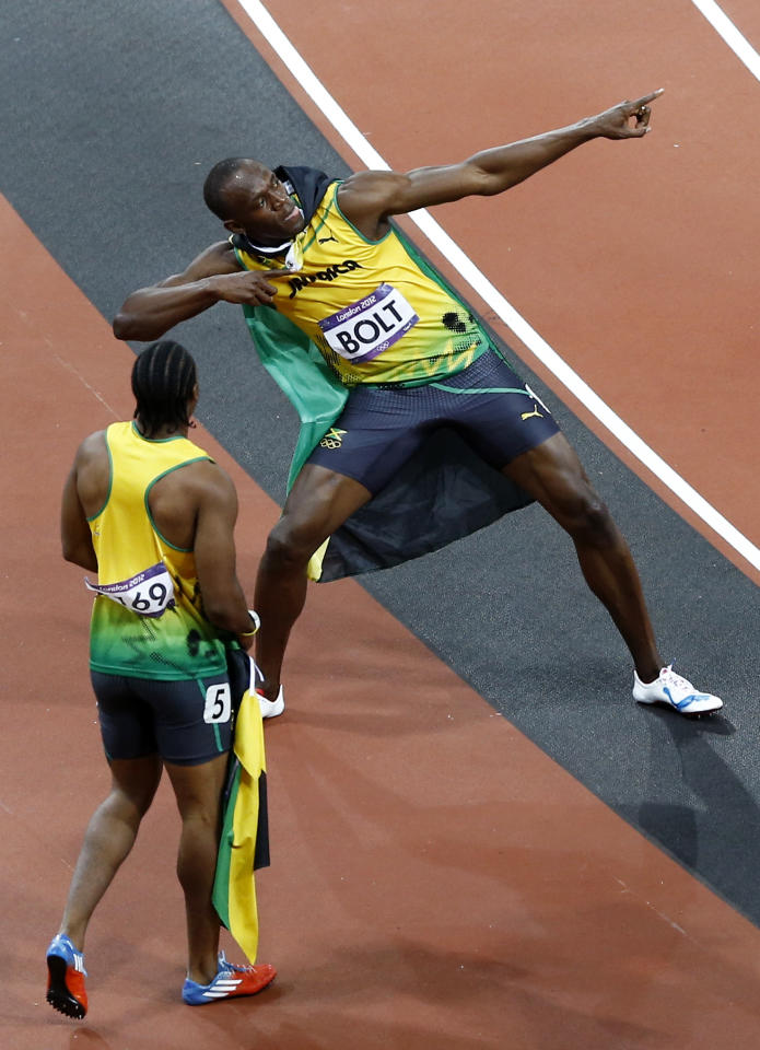 Jamaica's Usain Bolt, right, celebrates winning gold alongside silver medallist Yohan Blake of Jamaica, left, following the men's 100-meter final during the athletics in the Olympic Stadium at the 2012 Summer Olympics, London, Sunday, Aug. 5, 2012. (AP Photo/Daniel Ochoa De Olza)