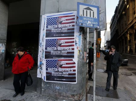 "Pedestrians stand next to posters that read ""Enough vultures, Argentina united for a national cause"" in Buenos Aires"