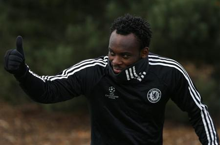 Michael Essien of Chelsea gives a thumbs up as he arrives for a team training session at their training facility in Stoke D'Abernon, south of London