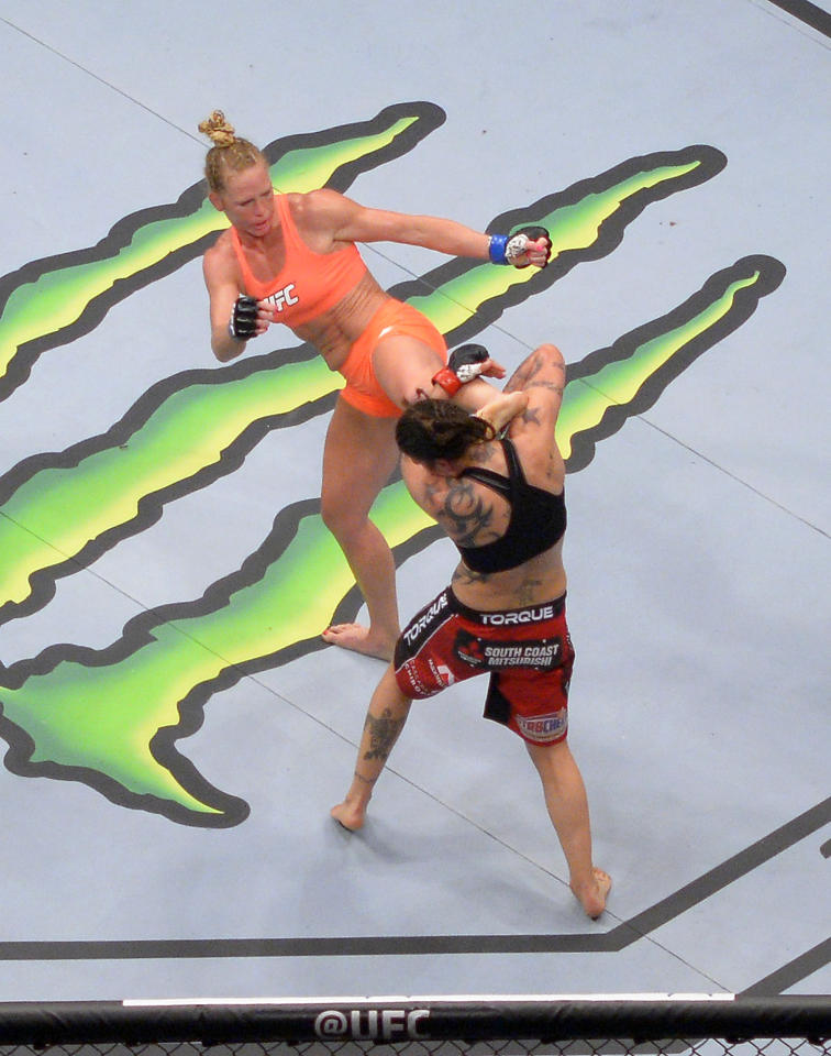 Holly Holm, top, connects with Raquel Pennington during a UFC 184 mixed martial arts bantamweight bout, Saturday, Feb. 28, 2015, in Los Angeles. Holm won by split decision. (AP Photo/Mark J. Terrill)