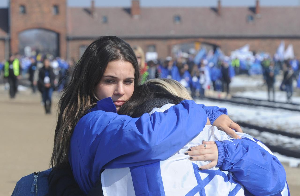 Young people hug each other during the March of the Living in Oswiecim, Poland, Monday, April 8, 2013. Jews from Israel and around the world took part in the annual March of the Living on the 3km route from Auschwitz to Birkenau Nazi Death Camps, commemorating the Holocaust victims. (AP Photo/Alik Keplicz)