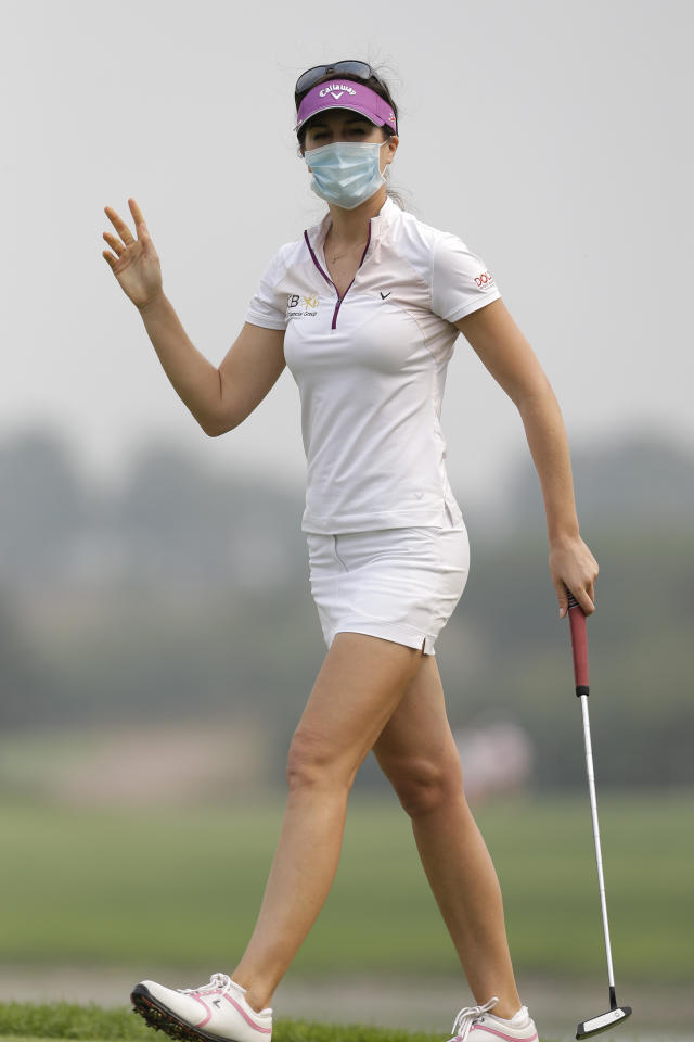 Germany's Sandra Gal, wearing a mask, gestures on the third green on a hazy day during the final round of the Reignwood LPGA Classic golf tournament at Pine Valley Golf Club on the outskirts of Beijing, China, Sunday, Oct. 6, 2013. Fog and pollution descended on northern China on Sunday, forcing international golf and tennis players to play in hazardous smog and leading to flight cancellations and road closures as millions of Chinese headed home from a national holiday. (AP Photo/Alexander F. Yuan)