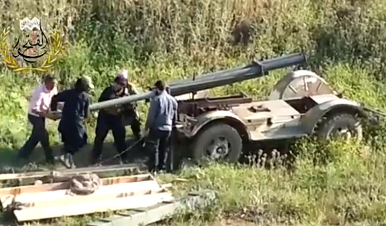 This image taken from video obtained from Ugarit News, which has been authenticated based on its contents and other AP reporting, shows Syrian rebels preparing to fire a rocket at Mannagh air base in Aleppo province, Syria, Monday, May 13, 2013. The Syrian government wants more details before deciding whether to take part in a proposed U.S.-Russian initiative to negotiate a peaceful end to Syria's crisis, the country's information minister said, staking out a similar position to the main opposition group.(AP Photo/Ugarit News via AP video)