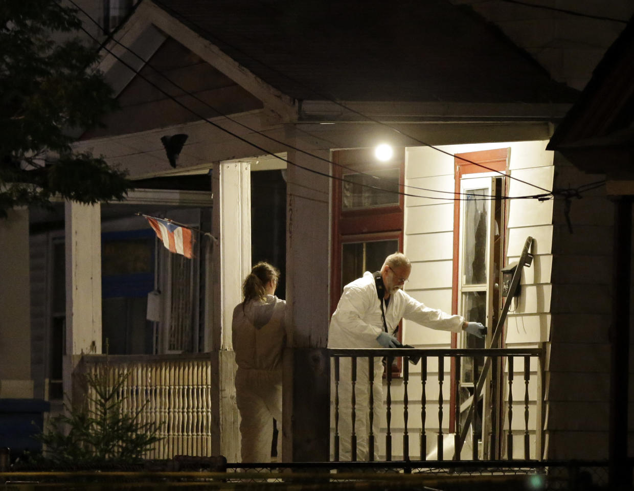 Investigators enter a house on the west side of Cleveland Monday, May 6, 2013 where police say three women were found. The women who went missing separately about a decade ago, when they were in their teens or early 20s, were found alive in the house, and a man was arrested. (AP Photo/Mark Duncan)