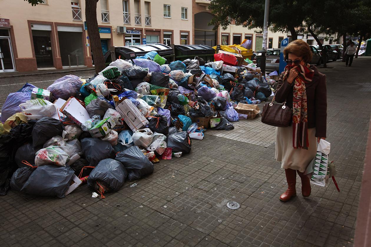 A woman covers her nose as she walks past garbage piled up in the middle of the street in Jerez de la Frontera, Cadiz province in Andalucia, southern Spain.